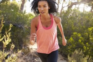 Determined young black woman jogging in a forest, close up