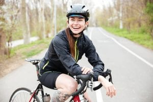 Happy beautiful young woman in bicycle helmet on bike