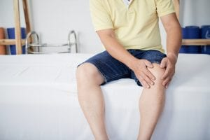 Crop man touching aching knee