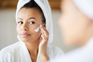 Mixed Race Woman Applying Face Cream