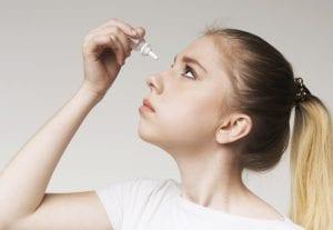 Young girl using disease contact eye drop