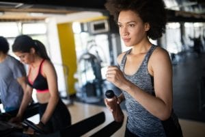 Young woman running on a treadmill in health club