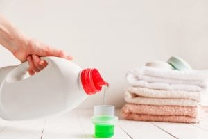 Close up of female hands pouring liquid laundry detergent