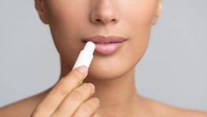 Girl applying hygienic lip balm on grey background